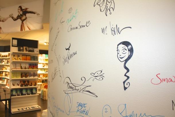Kirjailijoiden nimikirjoituksia kirjakaupan seinällä. Kuva: Reeta /Les! Lue!